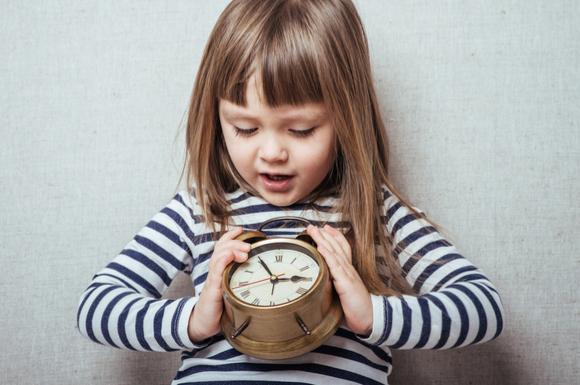 アナログ時計を見て時間を読んでいる子供