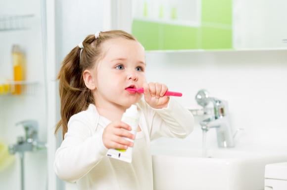 歯ブラシをくわえている子供