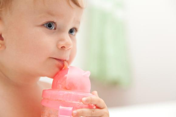 ストローマグで飲み物を飲んでいる赤ちゃん