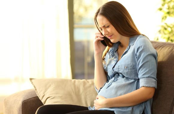 緊急事態で救急車に電話している妊婦さん