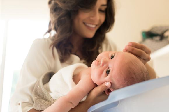 ベビーバスで赤ちゃんの沐浴を行っているママ