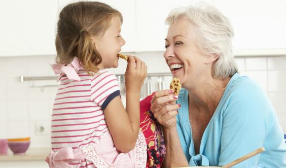 孫にお菓子をあげる祖母