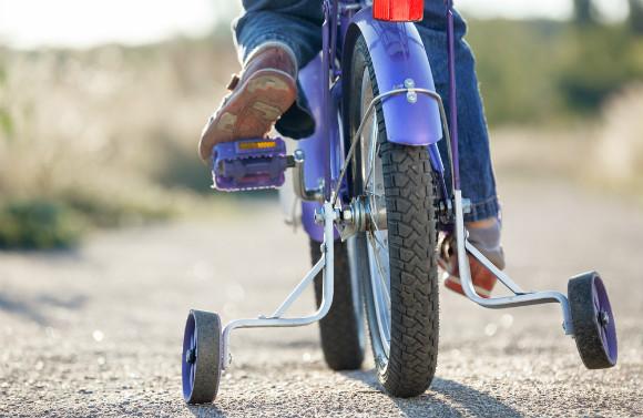 補助輪つきの自転車に乗る子供