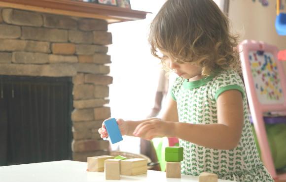 木製の積み木で遊んでいる子供