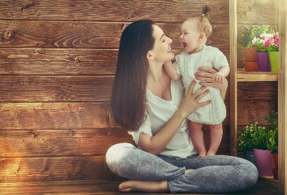 赤ちゃんの成長記録を母子手帳にとっているママ