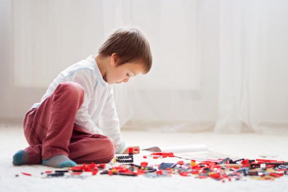 4際の子供が説明書を見ながら一生懸命ブロックで作品を作っている様子