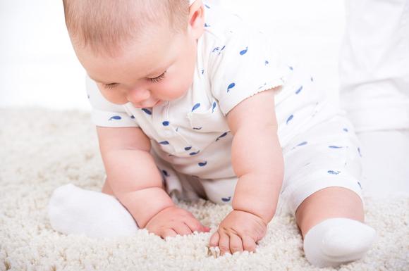 一生懸命一人でお座りをしようとしている赤ちゃん