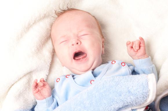 寝ながら泣きわめいている子供