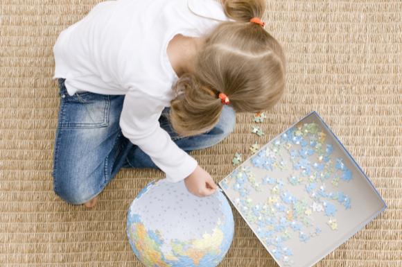 世界地図のパズルを集中して行っている子供