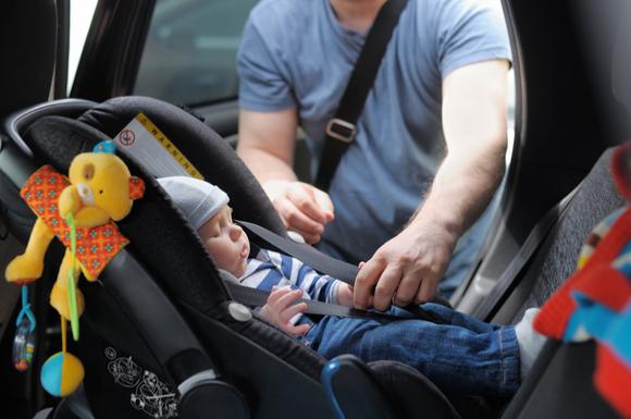 チャイルドシートに周辺おもちゃをつけてもらっている赤ちゃん