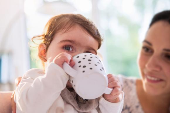 コップ飲みを練習している赤ちゃんと教えているママ