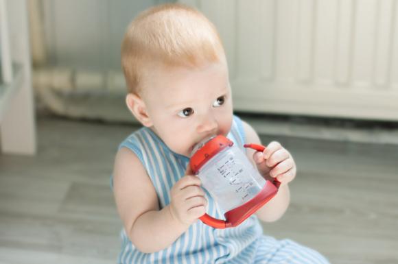 ストローマグで飲み物を飲んでいる赤ちゃんの様子