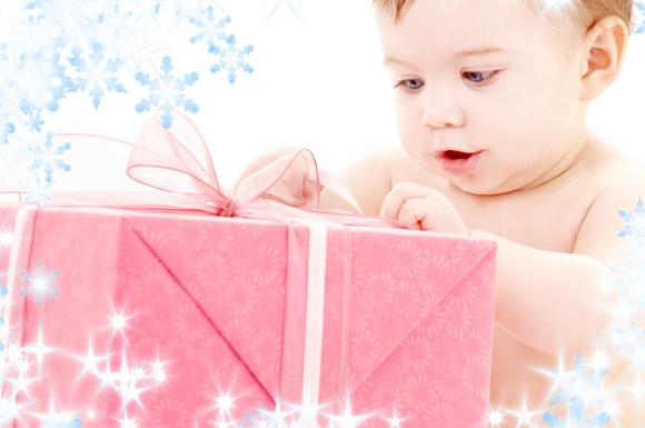 出産祝いを嬉しそうに見ている女の子の赤ちゃん