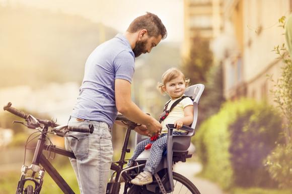 自転車のチャイルドシートに子供を乗せている様子