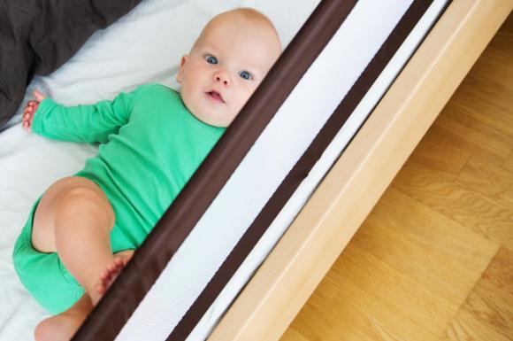 添い寝グッズを活用して赤ちゃんをベッドに寝かせている様子