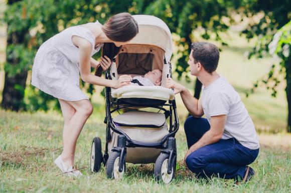 ベビーカーでお散歩している赤ちゃんと夫婦