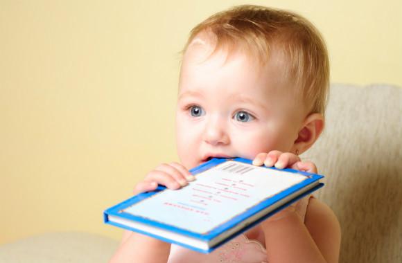 本などの紙を食べようとしている子供