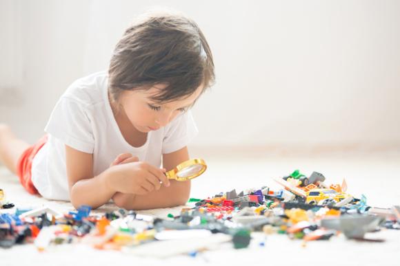 5歳の子供が様々な大きさや形のブロックで集中して遊んでいる様子
