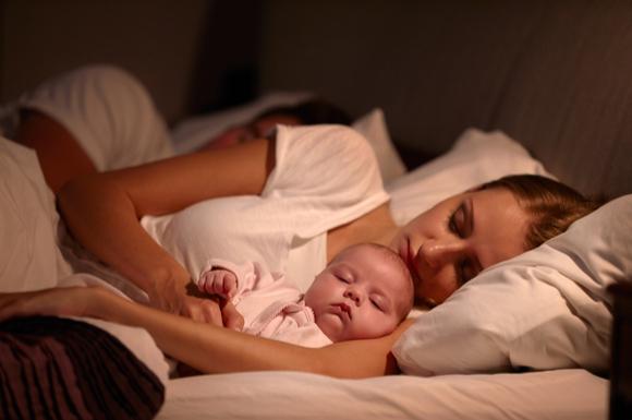 赤ちゃんとベッドで添い寝している様子